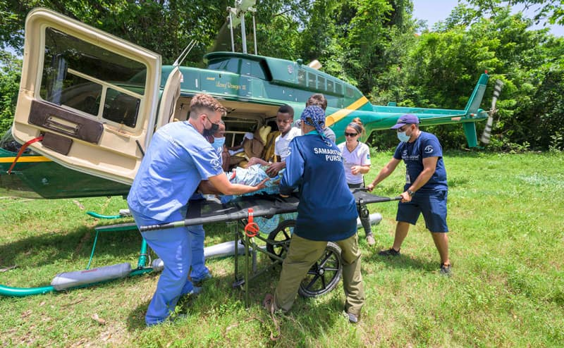 Our DART team transports a patient from a helicopter to our Emergency Field Hospital