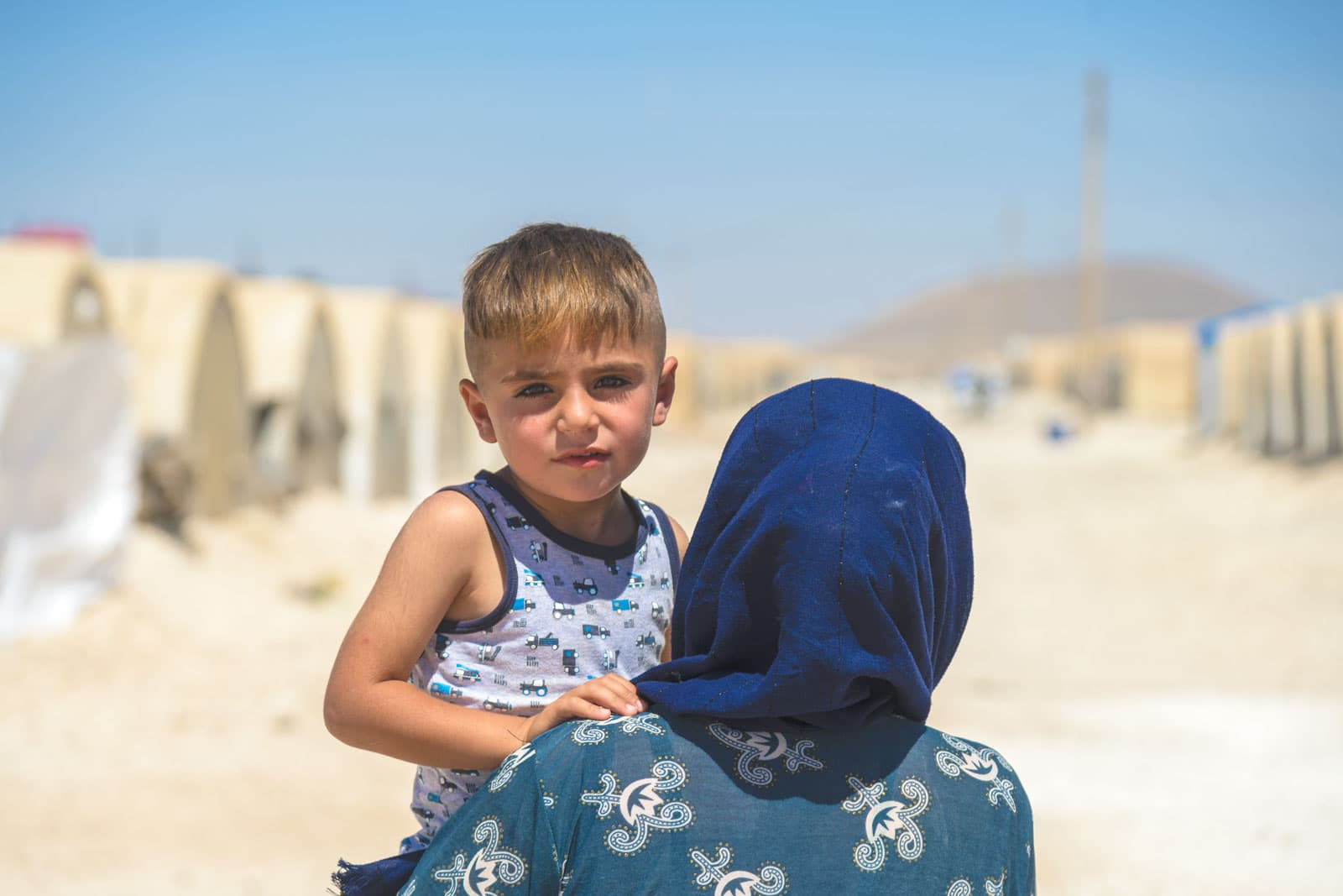 A Syrian mother carrying her son