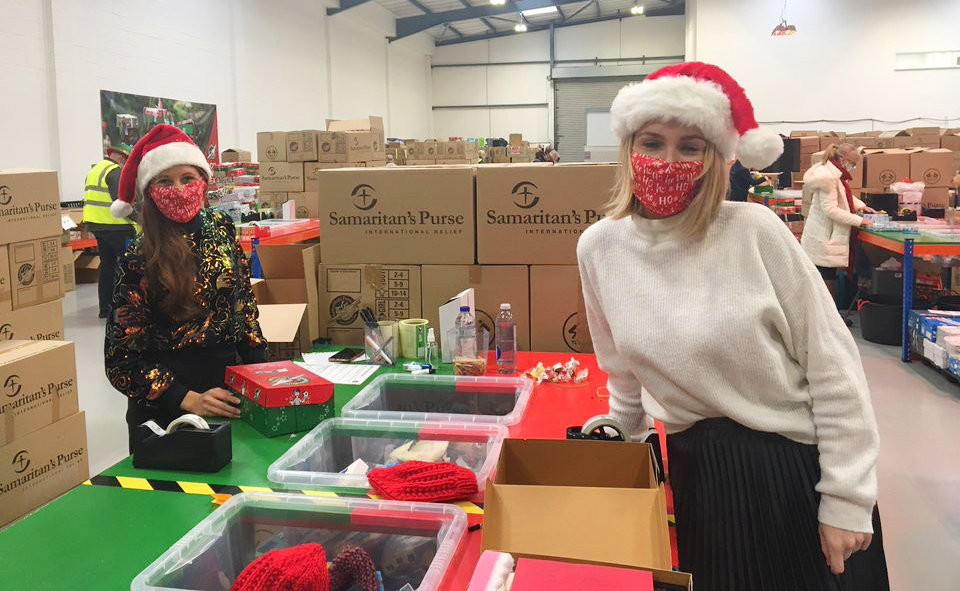 volunteers carefully packing shoeboxes