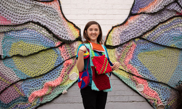 An artist at heart, Alathia displays an array of purses that she and her friends have made against the backdrop of a Fort Worth artist's depiction of a butterfly