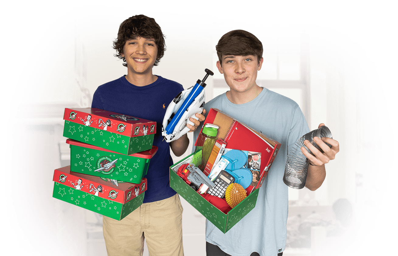 two student volunteers holding packed boxes